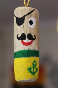 Treibholz mit einer Ringöse und Acrylfarben